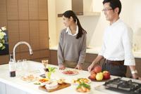 キッチンに立って微笑む夫婦