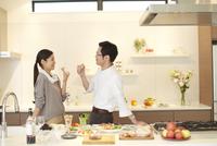 キッチンで食事をつまみ笑い合う夫婦