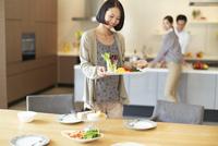 テーブルに食事を運ぶ女性