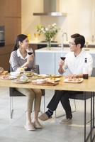 テーブルでワインを手に会話する男女