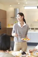 食事の皿を持って横を向いて笑う女性