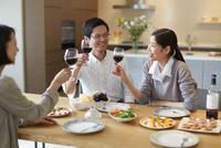 ホームパーティでワインを手に会話する男女三人