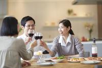 ホームパーティでワインを手に乾杯する男女三人