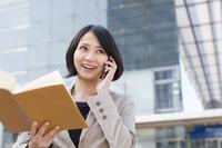 ビルの前で電話するビジネス女性