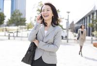 立ち止まって電話をするビジネス女性 33000000544| 写真素材・ストックフォト・画像・イラスト素材|アマナイメージズ