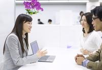 パソコンを使って接客するビジネス女性
