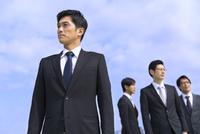 青空を背景に立つ4人のビジネス男性