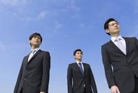 青空を背景に立つ3人のビジネス男性