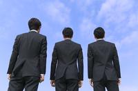 青空を背景に立つ3人のビジネス男性の後ろ姿