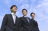 青空を背景に笑う3人のビジネス男性