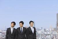 青空とビルを背景に笑う3人のビジネス男性