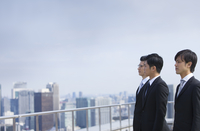 ビル群を見つめるように立つビジネス男性3人