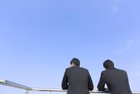 景色をながめるビジネス男性2人の後ろ姿