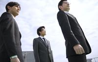 遠くを見ながら立つビジネス男性3人