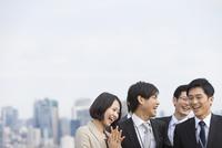 ビル群を背景に笑い合うビジネス男女