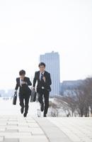 走るビジネス男性2人