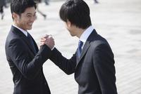 笑顔で手を組むビジネス男性2人