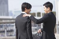 肩に手をかけて笑い合うビジネス男性2人
