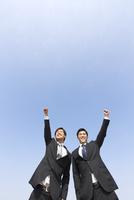 青空を背景にこぶしを上げるビジネス男性2人
