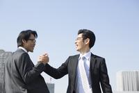 手を組んで喜ぶビジネス男性