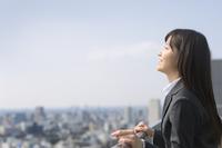 屋上で上を向いて微笑むビジネス女性