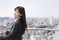 屋上で遠くを見ながら微笑むビジネス女性