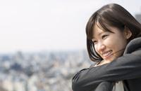 柵に肘をかけて微笑むビジネス女性 33000000671| 写真素材・ストックフォト・画像・イラスト素材|アマナイメージズ