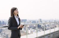 屋上でスマートフォンを手に上を見るビジネス女性