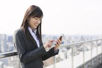 屋上でスマートフォンにタッチするビジネス女性