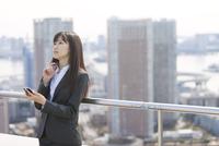 屋上でスマートフォンを手に考えるビジネス女性