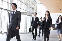 ビルのエントランスを歩くビジネス男女 33000000701| 写真素材・ストックフォト・画像・イラスト素材|アマナイメージズ