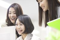 パソコンを見て喜ぶビジネス女性3人