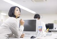 デスクで上を向いて考えるビジネス女性