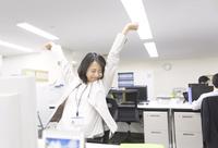 オフィスで伸びをするビジネス女性