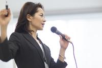 マイクを手に講義するビジネス女性 33000000756| 写真素材・ストックフォト・画像・イラスト素材|アマナイメージズ