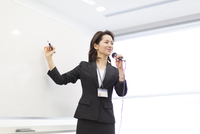 マイクを手に講義するビジネス女性