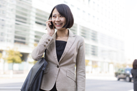 スマートフォンで話すビジネス女性 33000000767| 写真素材・ストックフォト・画像・イラスト素材|アマナイメージズ