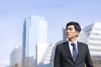 ビルを背景に上を見るビジネス男性