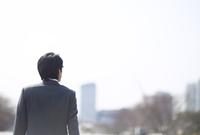 遠くを眺めるビジネス男性の後ろ姿