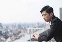 屋上で景色を眺めるビジネス男性