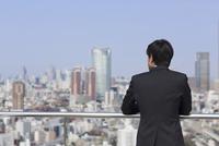 屋上でビル群を眺めるビジネス男性の後ろ姿