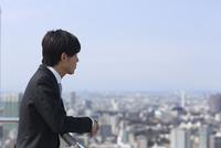 屋上でビル群を眺めるビジネス男性