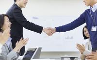 会議で握手するビジネス男性2人