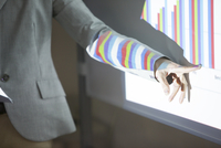 会議でグラフの説明をするビジネス女性の手