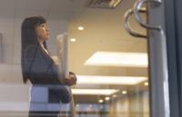 封筒と筒を持って上を向くビジネス女性