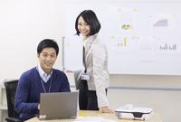 ノートパソコンを前に微笑むビジネス男女