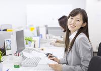 デスクで資料を手に微笑むビジネス女性