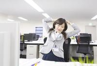 デスクで伸びをするビジネス女性