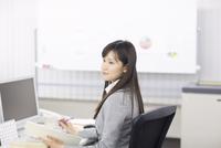 デスクで遠くを眺めるビジネス女性