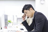 デスクで資料を見て考えるビジネス男性